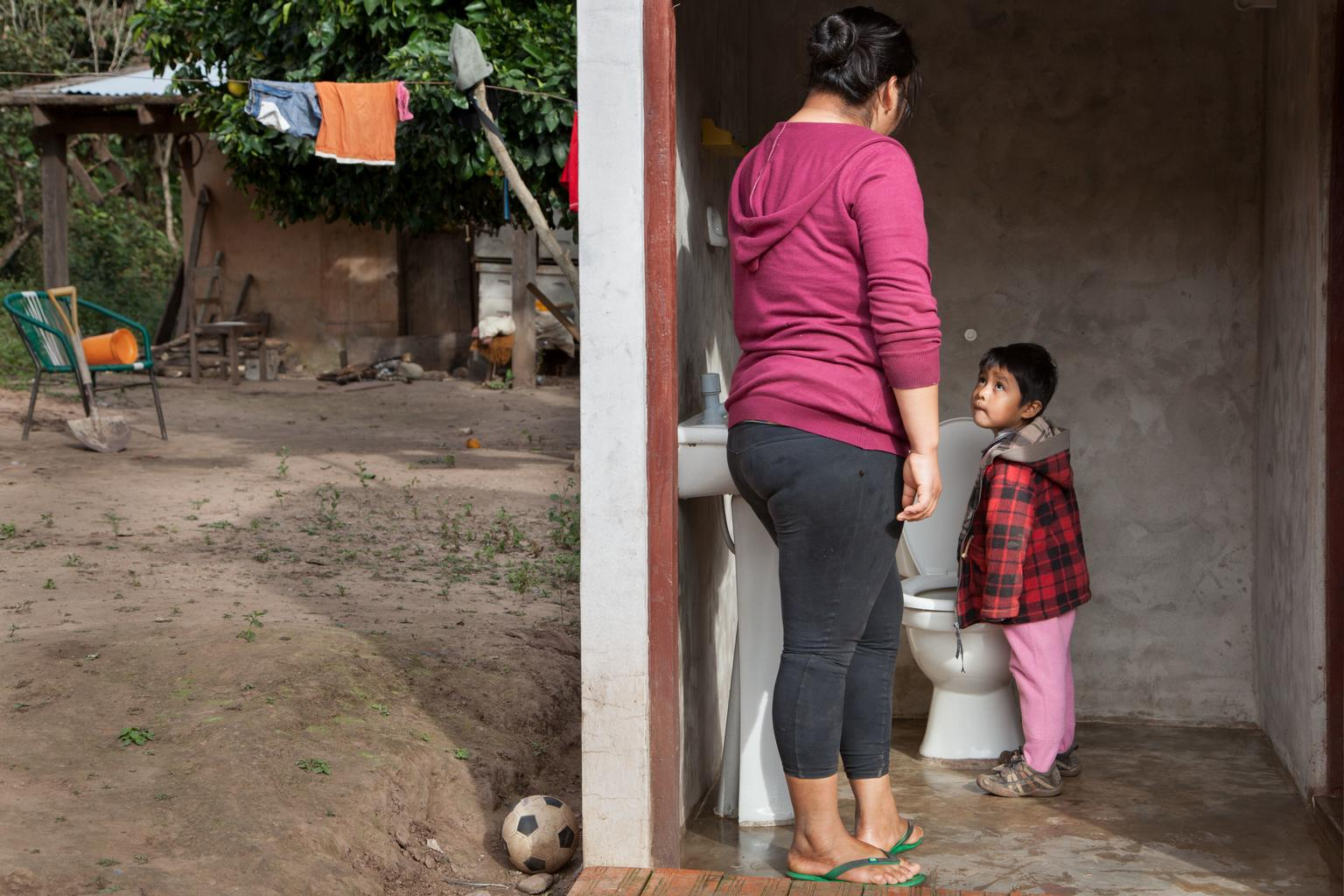 A mother stands with her son beside a new toilet